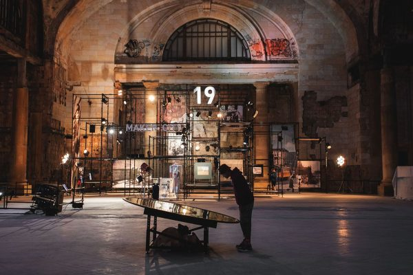 Man looking at exhibit in industrial train station.